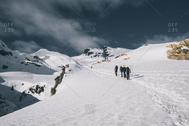 Hikers on snowshoes toward a mountain summit against snowcapped peaks