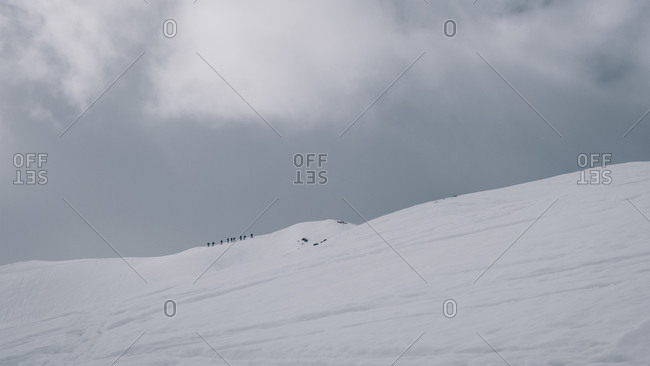 Alpinists trying to summit a snowcapped mountain summit on cloudy day