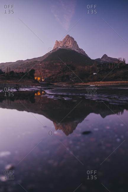 Scenic mountain reflected on a lake during dusk in the Pyrenees, Spain