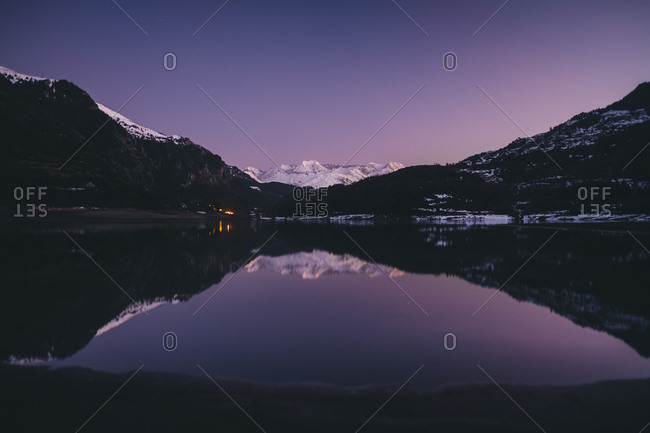 Scenic snowcapped mountain reflected on a lake during dusk in Pyrenees