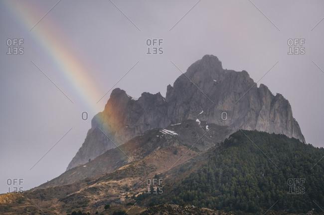Rainbow against mountain summit during rainy day, Pyrenees, Huesca