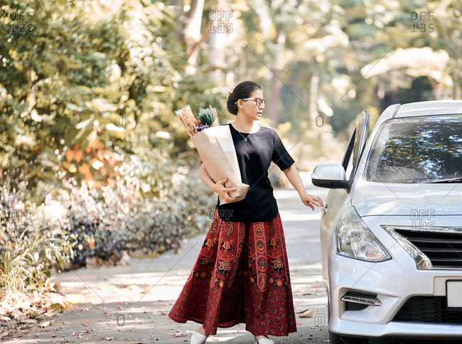 A woman hold a paper bag of dry flower and back to car after shopping