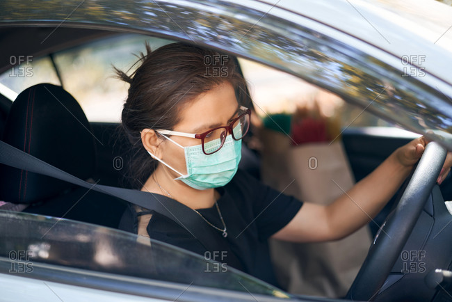 Woman wears a surgical mask and driving a car during the covid-19