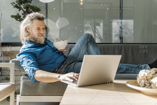 Mature man with a beard smiling and working with his laptop on a sofa