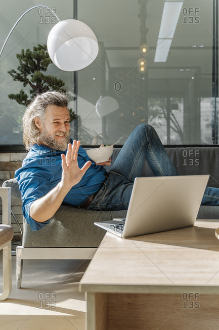 Mature man with a beard eating a salad and looking at his laptop on a
