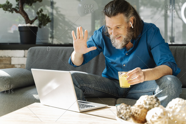 Mature man with a beard drinking orange juice and looking at his laptop