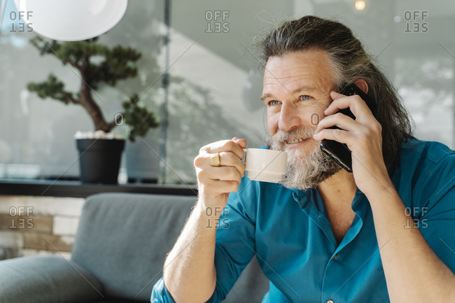 Mature man drinking a coffee and talking on the phone sitting on a sofa in his living room. Business concept