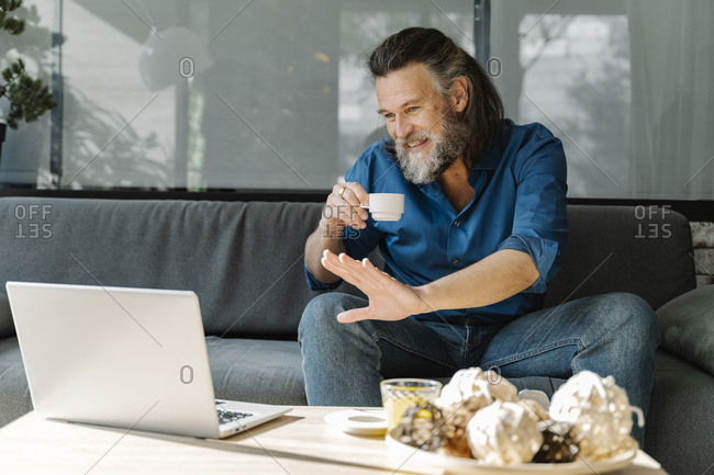 Mature man with a beard drinking a cup of coffee and talking on a video call in front of his laptop sitting on a sofa in his living room. Business concept