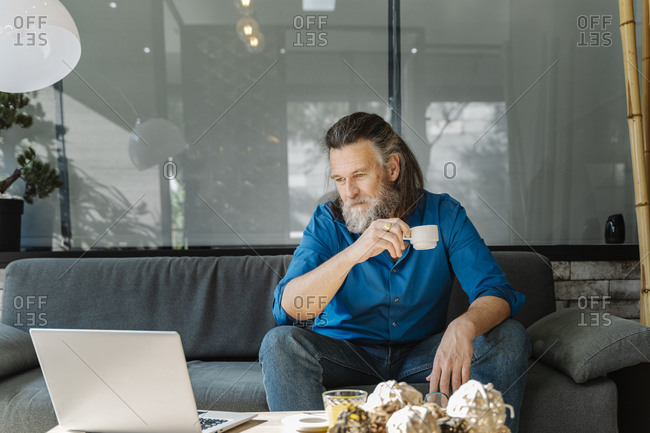 Mature man drinking a coffee and talking on the phone sitting on a sofa