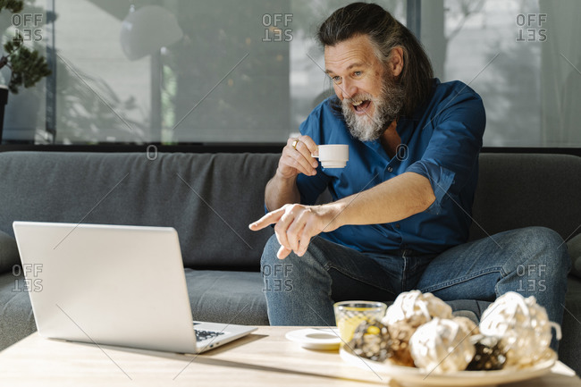 Mature man with beard talking on the phone and drinking coffee sitting