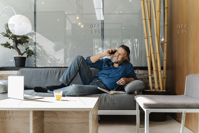 Mature man with a beard sitting on a sofa and looking at his smartphone