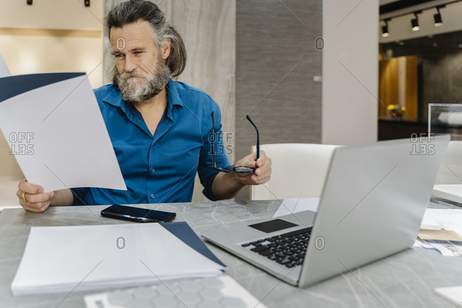 Bearded mature man reviewing some documents at his desk in front of his laptop at home. Business concept