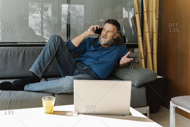 Mature man with a beard talking on the phone on a sofa in front of his laptop. Business concept