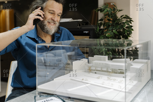 Mature man with a beard talking on the phone and looking at a model of a building. Architecture concept