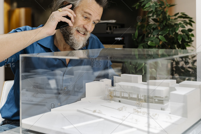 Mature man with a beard talking on the phone and looking at a model of