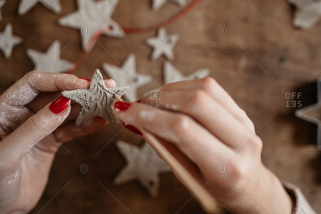 hands of young woman creating clay star ornaments for Christmas