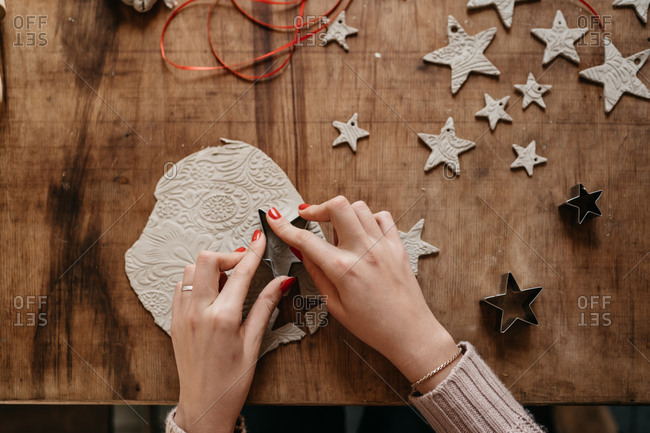 hands of young woman sitting at table creating ornaments with clay