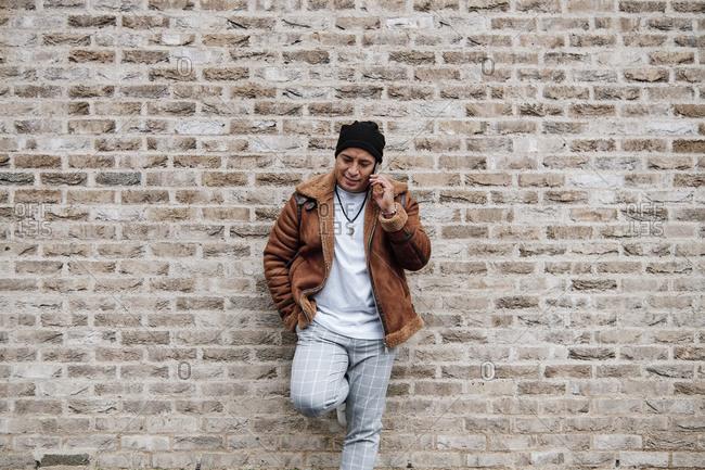 stylish Latino man talking on the phone against a brick wall