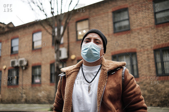 middle aged Latino man with a serious expression wearing a face mask outside looking at camera