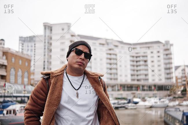 Latino man wearing sunglasses in the city looking at camera