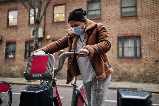 young man wearing a face mask grabbing a bicycle on the street