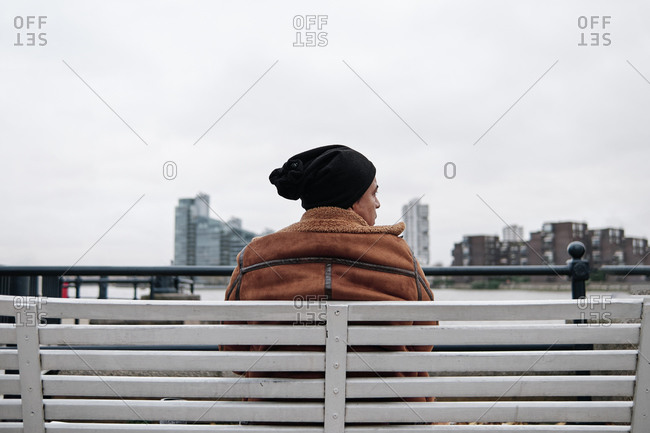 young man sitting on a bench staring at the city with a serious face