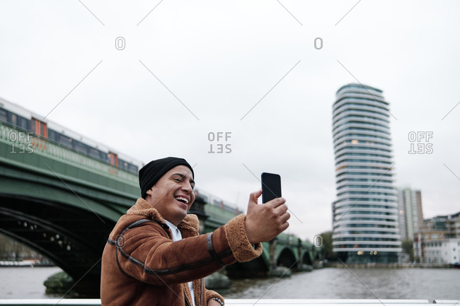 Latino man chatting on the phone outside next to the river