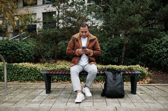 Latino man checking his phone while sitting on a bench