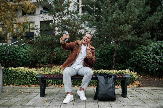Latino man sitting on a bench while taking a photo smiling and doing peace sign