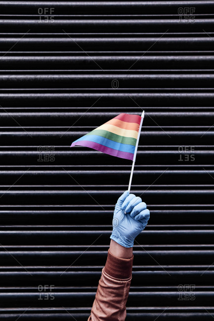 a hand holding a pride flag with a glove on. black background
