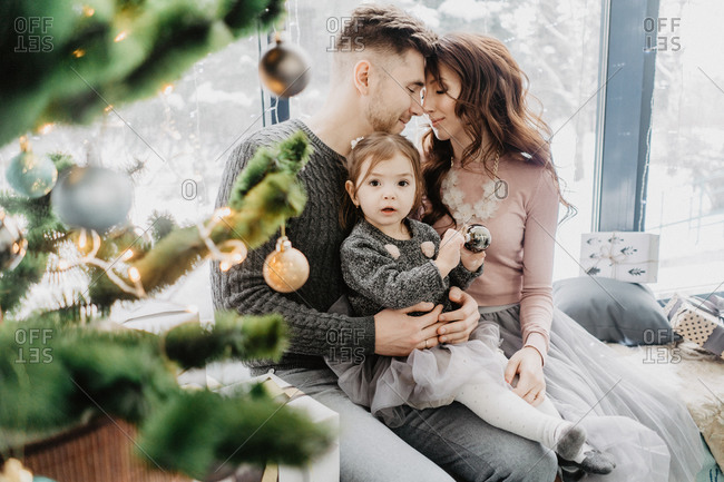 Young family with a daughter in festive outfits with a garland near the Christmas tree on New Years Eve