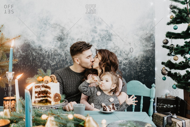 Young family with a daughter in festive outfits at a served table with candles, garlands, sparklers and a cake near the Christmas tree on New Years Eve