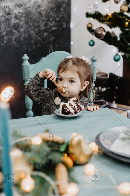 Little girl eating christmas cake on a set table on New Years Eve