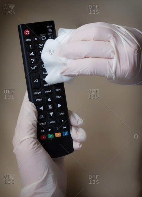 Hands Disinfecting A Television Remote Control. Covid-19