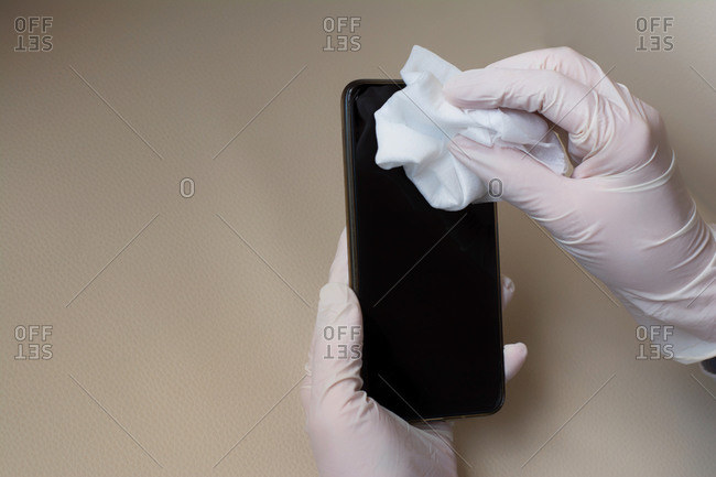 Hands Disinfecting A Mobile Phone. COVID-19