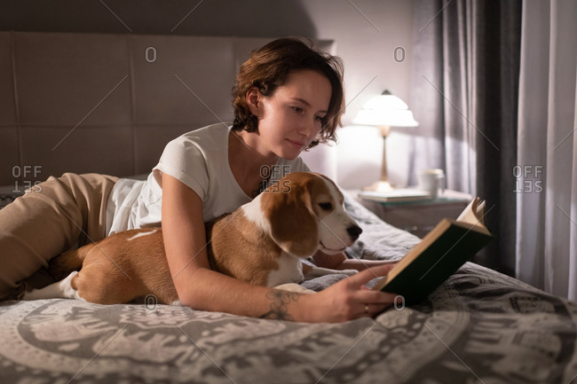 Young woman with Beagle reading book on bed