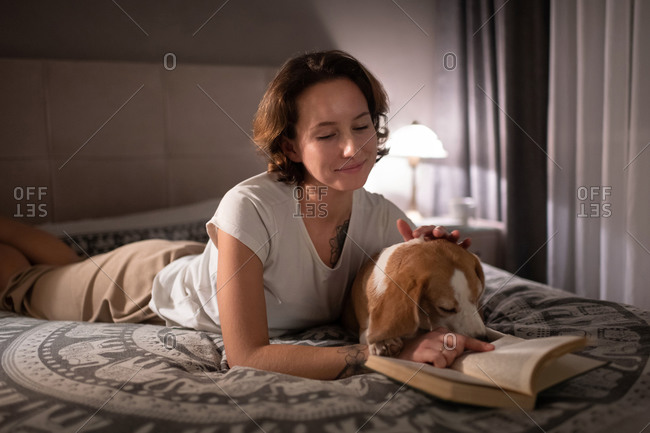 Happy female owner with dog reading book