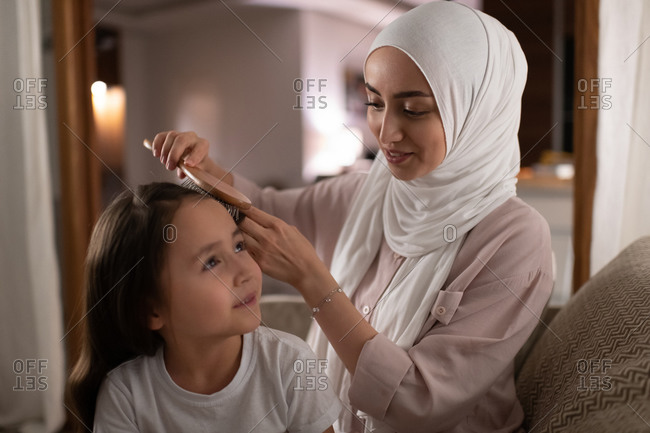 Glad Muslim mother doing hair of daughter