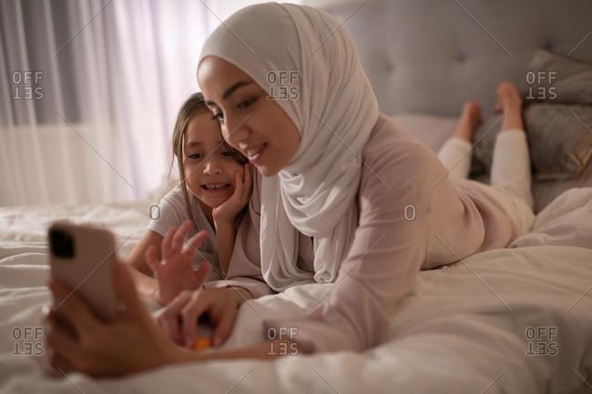Happy Muslim woman and girl having virtual meeting