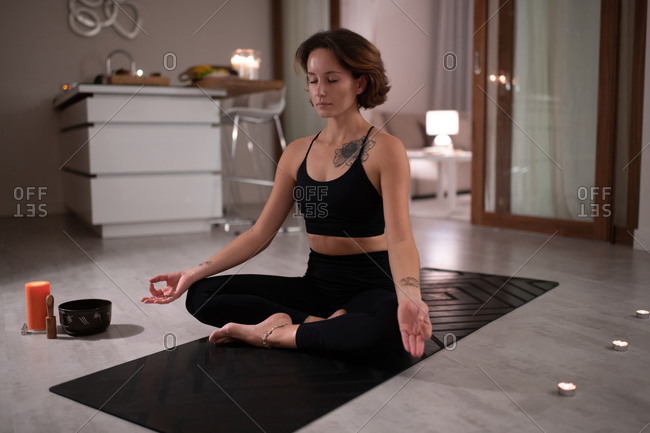 Young woman meditating near candles