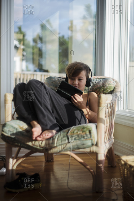 Young boy sits in a chair playing with an electronic device