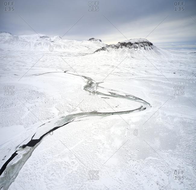 Frozen river in mountainous valley in winter