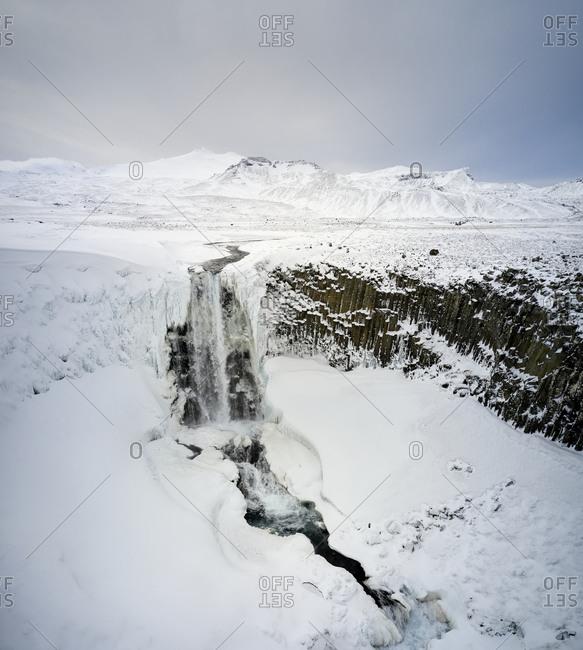 Waterfall in snowy highland terrain in winter