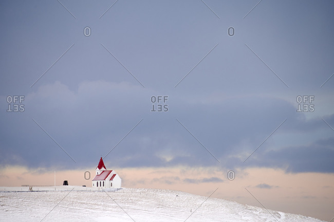 Church on snowy hill at sundown