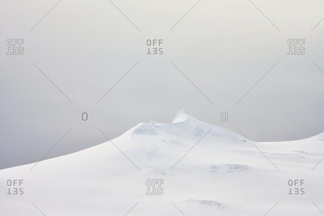 Snowy mountain peak against gray sky