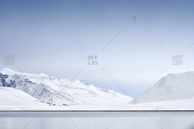 Northern landscape of snowy mountains on seashore