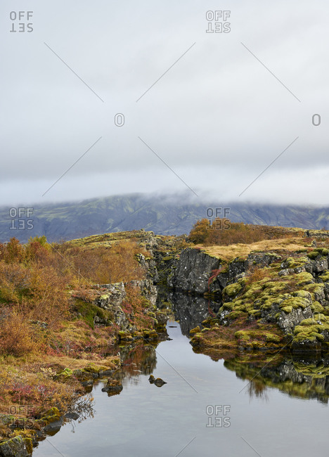 Mossy cliffs and water on autumn day