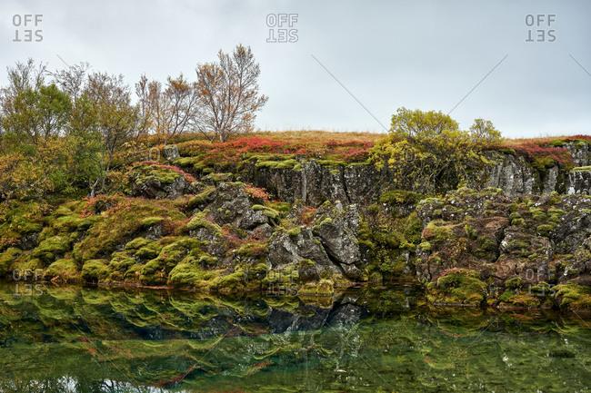 Picturesque autumn scenery of lake with rocky shore and colorful plants