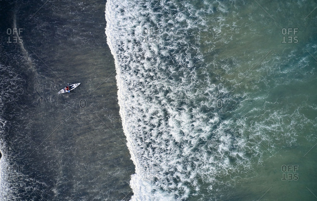 Cold waves of ocean with lonely kayaker