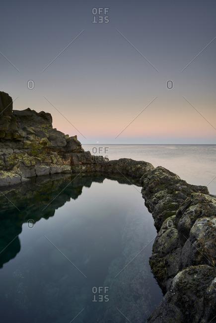 Peaceful lagoon against sunset sky